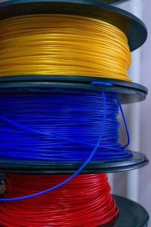 3D printing material, ABS filament, PLA (Polylactic Acid),  PVA Filament.  Colored polymer in coils on the shelves.