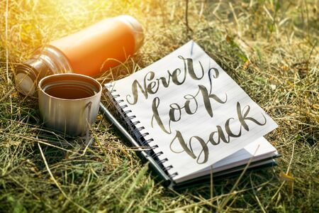 Never look back word written in white notebook with pen and red cup thermos on the green grass. Outdoor Concept hand writing showing Never Look Back, No regrets.