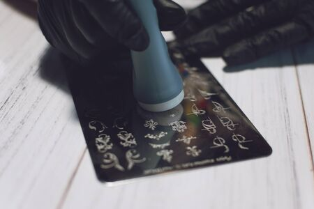 Nail Art Stamping process. Manicure master makes Stamping with nail gel polish, Stamping Plates and Transparent Stamper Scraper.