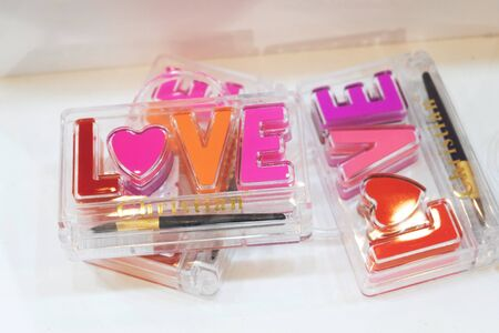 Kiev, Ukraine – 19 September, 2018: Bright lip gloss in the shape of the word love. Multicolored cream lipstick pack.