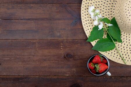 Summer background with straw hat, strawberries in cup and white flowers with green leaves on wooden background. Summer berry vitamin background. Flat lay. Summer concept. Reklamní fotografie