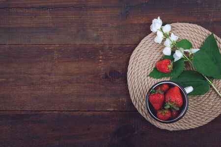 Summer background with straw round tray, strawberries in cup and white flowers with green leaves on wooden background. Summer berry vitamin background. Flat lay. Summer concept