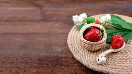 Summer background with straw round tray, strawberries in clay cup and white flowers with green leaves on wooden background. Summer berry vitamin background. Flat lay. Summer concept.