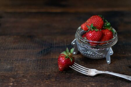 Rural fresh organic strawberry in metal bowl and fork on dark wooden rustic table. Red raw strawberry on a dark wood background. Selective focus. Reklamní fotografie