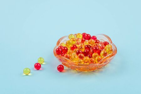 Yellow and red vitamin fat-soluble vitamins in glass plate on blue background. Variety of dietary supplements close up.