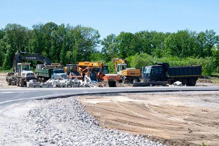 KROPIVNITSKIY, UKRAINE – 27 MAY, 2018: Road repair concept. Road construction automotive equipment on highway. Tractors, trucks, roller on the road repair site. Fresh asphalt construction. New road.