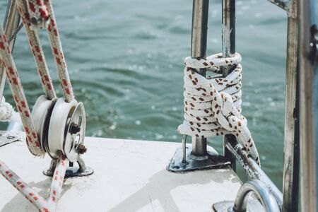 Rope on a yacht. Yacht rope cleat and sunlight. Sailboat winch and rope yacht detail. Yachting.