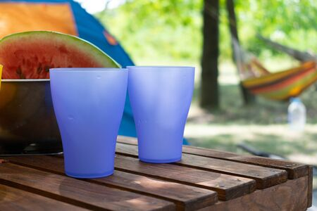 Colored plastic purple glasses, picnic utensils against tent and hammock background in Summer day.  picnic basket with plastic cutlery and paper plates in outdoor setting. Reklamní fotografie