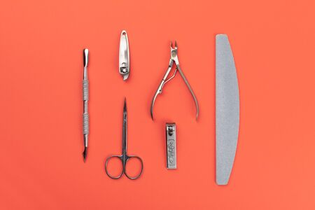 Equipment for cut manicure on coral background. Metal instruments for manicure. Nails salon and spa Flat lay.