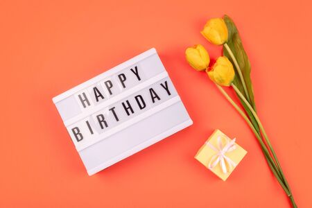 Celebration Happy birthday gift flat lay background. Light box with text Happy birthday and bouquet of yellow tulips on coral background.
