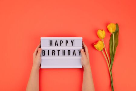 Happy birthday flat lay. Children hands holding light box with text Happy birthday and bouquet of yellow tulips on coral background.