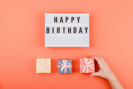 Happy birthday gift flat lay background. Children hands holding gift box with ribbon bow and light box with text Happy birthday on coral background.