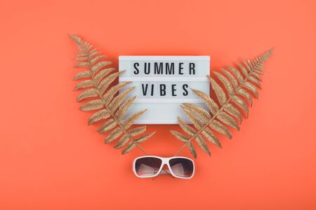 Summer vacations trip flat lay with Summer vibes text on light box, golden tropical leaves and Trendy white sunglasses. Colorful Hot Summer, vacations, travel concept.