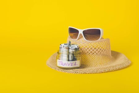 Summer weekend travel vacation concept. Beach accessories, straw hat, white sunglasses and save money glass jar with dollars banknotes on yellow background.