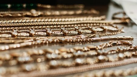 luxury gold jewelry chains, bracelets background, selective focus. Stylish beautiful bijouterie hanging on the stand in the accessories store. Various Jewelry bijouterie. Reklamní fotografie