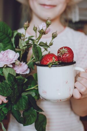 Girl child holding fresh red organic strawberries in white enameled cup and bouquet of rose. Fresh organic Strawberries in children hands. Summer weekend garden background.