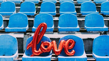 Love red foil balloon on blue stadium seats. Letter-shaped balloons forming the word love lifestyle background