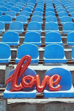Love red foil balloon on blue stadium seats. Letter-shaped balloons forming the word love lifestyle vertical background