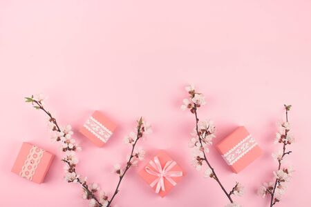 Flat lay with pink gift boxes and blooming cherry sakura flowers on pastel background. Birthday gift girl pink background with copy space. 写真素材