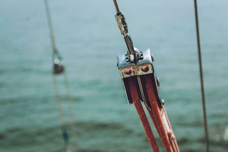 Close up of yacht equipment. Part of yacht with red ropes and capstan. Sailing boat pulley with nautical rope. Marine background. Stok Fotoğraf