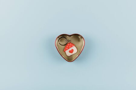 House shaped keychain with red heart in heart shaped metal box on blue background.