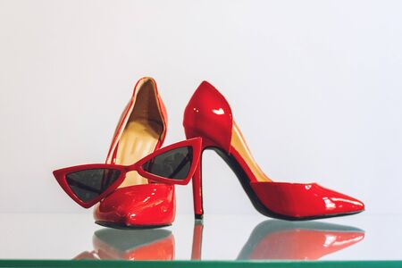 Female red fashion accessories. Red women heel shoes and trendy red cat eye sunglasses on the shelf in the store shop. Set of women fashion outfit. 写真素材
