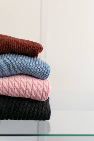 Fall winter fashion trends. Stack of cozy knitted sweaters in retail shop, store. Fashion shopping sale background with copy space.