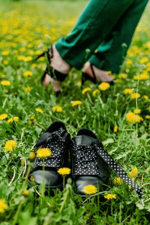 Comfortable shoes concept. Business woman changing shoes Work Heels from high heel to comfortable sneakers on green grass.