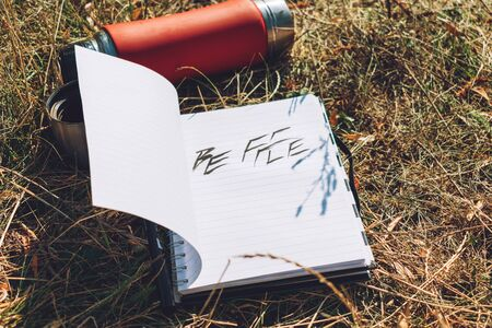 Be  free word written in white notebook with pen and red cup thermos on the green grass. Outdoor Concept hand writing showing Be  free, freedom, Adventure 写真素材