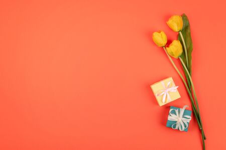 Yellow tulips flowers, gift box n coral background. Festive birthday flat lay. Greeting for Womens or Mothers Day. 写真素材