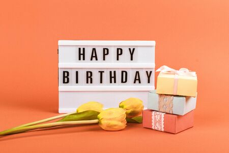 Happy birthday word light box, Yellow tulips flowers, gift boxes on coral background. Festive Greeting birthday background. 写真素材