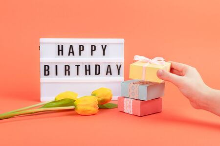 Happy birthday word light box, Yellow tulips flowers, gift boxes and child hand on coral background. Festive Greeting birthday background. 写真素材