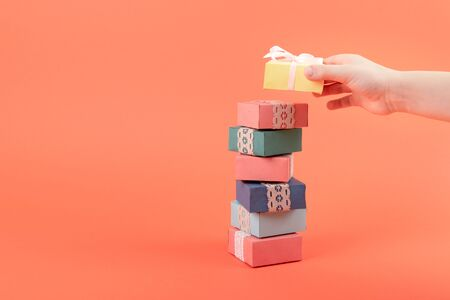 A stack of multi-colored gift boxes coral background. Many gift boxes with child hand. 写真素材