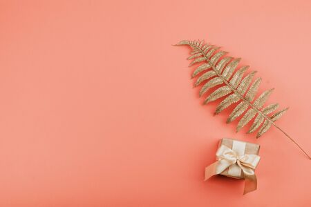 Gift box with bow and Golden palm leaves on coral background. Festive minimal background. 写真素材