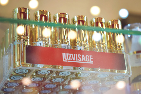 Kiev, Ukraine – 19 September, 2018: Belarusian cosmetics Luxvisage lipstick in gold cases. A lot of lipstick on a glass shelf in the store