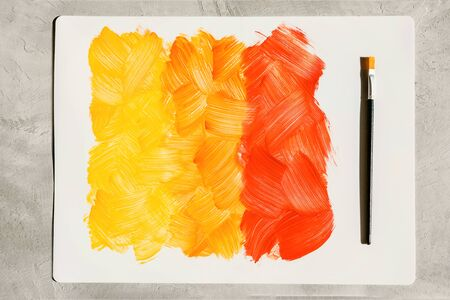 Action painting. Abstract Hand-painted yellow and orange art background. Multicolored paint strokes and brush.