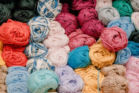 Different colored yarn balls in the shop. Multi-colored Yarn for knitting on shelf in store. Selective focus
