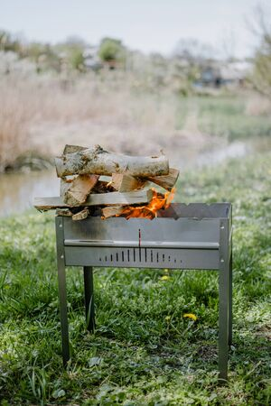 Metal portable barbecue with burning firewood and red flames. Picnic outdoor BBQ Barbecue. Bonfire for cooking meat. Fire and coal in the grill. Flaming wood with fire and ashes. Stock Photo