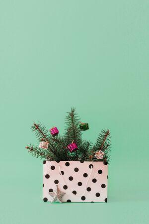 Weihnachtskomposition mit immergrünen Baumzweigen des Nadelbaums und Kugelball in der Geschenktüte Weihnachten und 2020 neues Jahr minimales Konzept auf Pastellhintergrund, Kopierraum