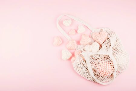 Reusable shopping net bag with white and pink knitted hearts on pastel background. Top view of eco friendly mesh shopping cotton bag. Ecological, Zero waste, No plastic concept.