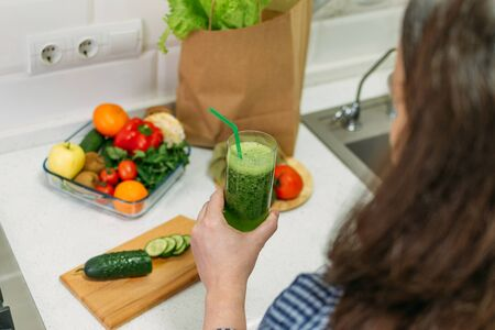 Benefits Of Cucumber juice. Green smoothies cooking for detox and weight loss. Glass of fresh cucumber juice on home kitchen table.