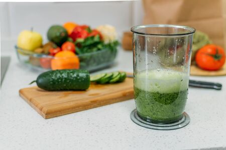 Benefits Of Cucumber juice. Green smoothies cooking for detox and weight loss. Glass of fresh cucumber juice on home kitchen table