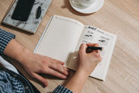 Bullet Journal Habit Tracker. Woman cross off day with routine in her Habit Tracker. Selective focus. Banque d'images