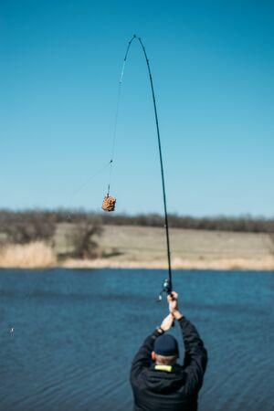 Feeder fishing. Carp Fishing Steel Basket Bait Feeder on rod close up. Male fisherman fishing at sun day on the lake.