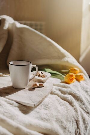 Morning routine, Miracle Morning, new day concept. Best ritual and habits. Cup of coffee, whole grain cookies, open notepad on wooden tray on the bed in the sun