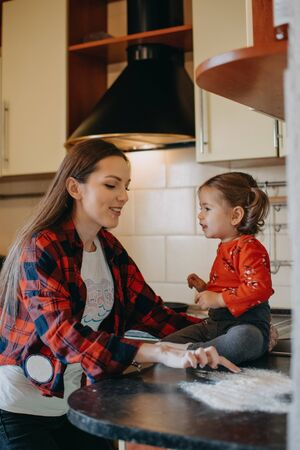 Activities for Kids in Coronavirus Quarantine. How Parents Can Keep Kids Busy and Learning in Quarantine. Mom and toddler daughter play in the kitchen