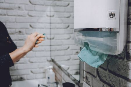 Coronavirus protection hand hygiene. Paper towels and alcohol gel antibacterial soap sanitizer in bathroom. Woman washes her hands and wipes with a paper towel.