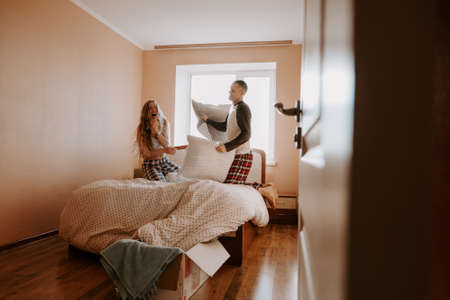 Isolating Together. Mother And Daughter Pillow Fight In Bed. Couple stay home. Family lockdown, how to emotionally prepare for coronavirus quarantine, self- isolation, Social Distancing.