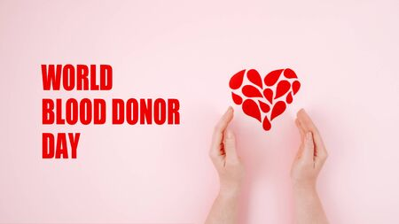 World Blood Donor Day. Blood donor day campaign for donation charity concept with red drops heart and hands. Giving blood saves lives