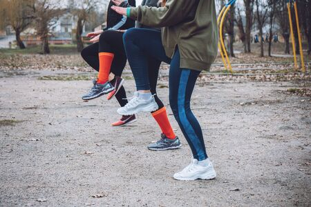 Outdoor gym fitness classes, outside workout. Fitness in the fresh air. Safer outside. Group fitness classes, HIIT training, Run Clubs, Strength Circuits. Close up sportswoman legs. 写真素材